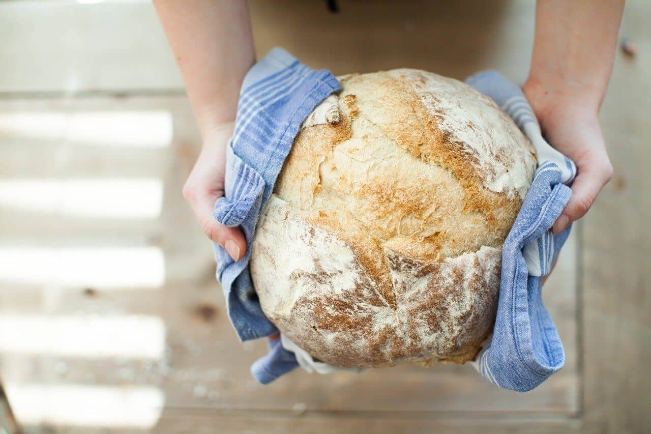 Hands holding baked white bread in a blue cloth