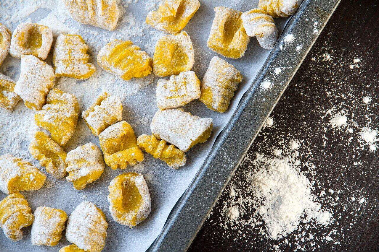 Homemade gnocchi on a tray with flour