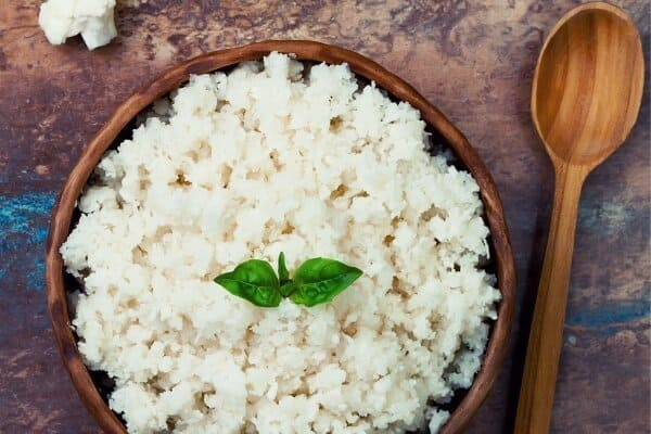 cauliflower rice in a brown bowl with spoon