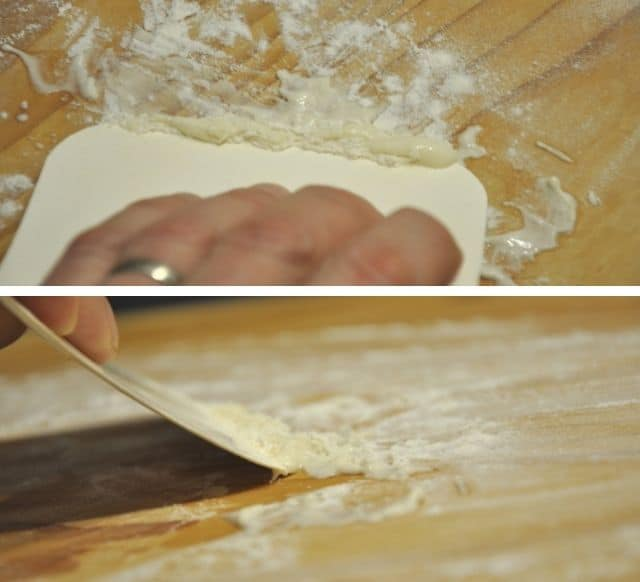 cleaning and scrapeing off dough from pasta board