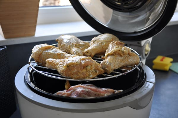 stacked chicken drumsticks on a rack in a basket style air fryer