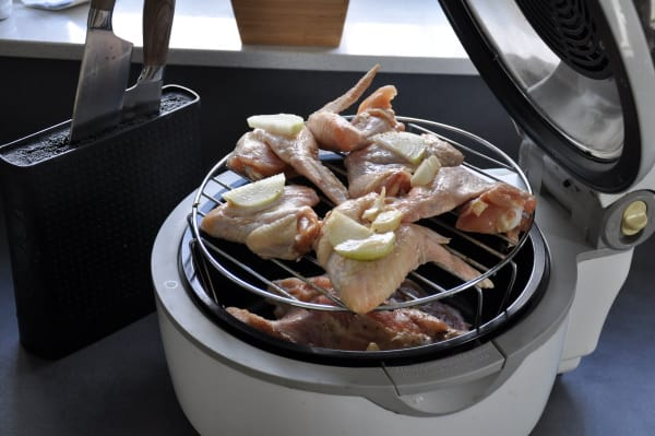 stacked chicken wings on a rack in a basket style air fryer
