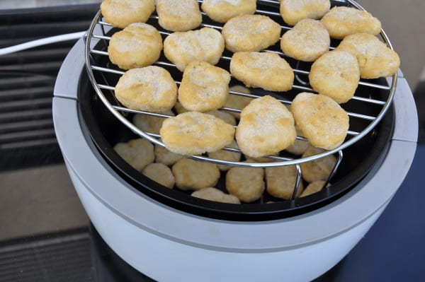 Stacked chicken nuggets in an air fryer with a rack