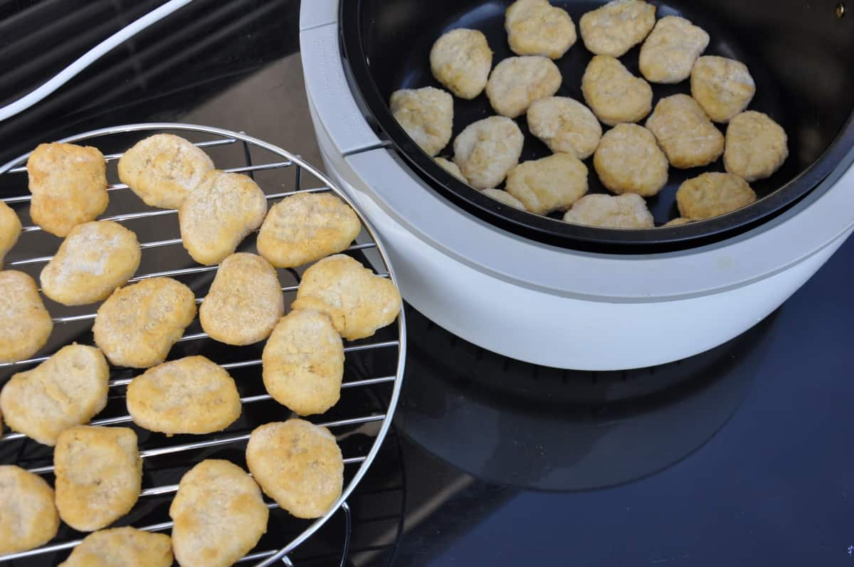 Stacked chicken nuggets on a rack and in the basket of an air fryer