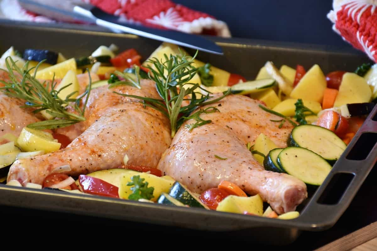 raw chicken and raw vegetables touching before roasting in a roasting pan